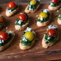 Sauteed Arugula and Cherry Tomato Crostinis with Blue Cheese Crumbles